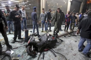 Motorcycle is seen amid residents inspecting a damaged area caused by two explosions in Beirut's southern suburbs