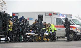 Emergency personnel transport an officer to an ambulance after reports of a shooting near the Planned Parenthood clinic Friday, Nov, 27, 2015, in Colorado Springs, Colo. Daniel Owen / AP