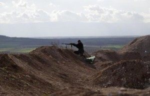 A rebel fighter from the Ahrar al-Sham Islamic Movement takes a position as he aims his weapon at Morek front line in the northern countryside of Hama March 16, 2015. REUTERS/Khalil Ashawi