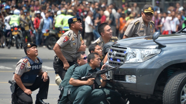 Indonesian police take position behind a vehicle as they pursue suspects after a series of blasts in Jakarta. (AFP/Getty Images)