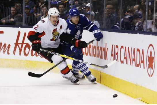 Ottawa Senators defenceman Dion Phaneuf, left, and Toronto Maple Leafs forward Ben Smith battle for the puck during the first period Saturday night. Photo Credit TODD KOROL / TORONTO STAR
