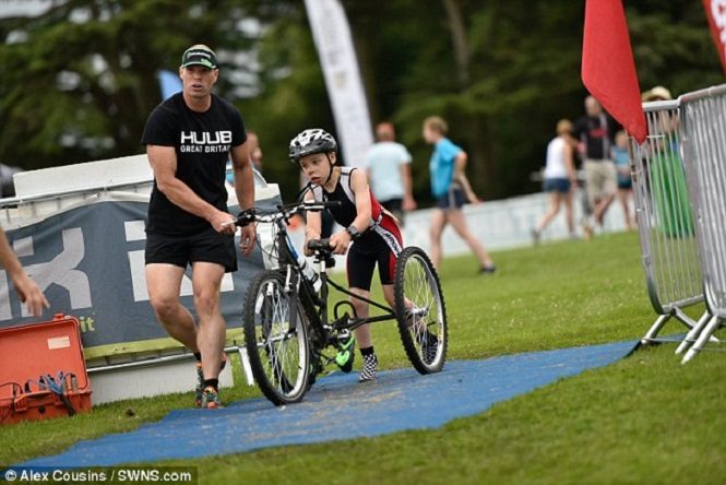 Boy, nine, battling cerebral palsy throws away walking frame to finish triathlon for 2nd year in a row and even knocks 7 minutes off his time